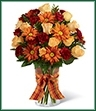 The Golden Autumn Bouquet exudes the warmth and comfort of the harvest season with each colorful bloom. Peach spray roses, burgundy mini carnations, butterscotch chrysanthemums and lush greens are arranged beautifully in a classic clear glass vase accented with an orange plaid ribbon around the neck, creating a truly wonderful bouquet that will send your sweetest sentiments to your special recipient for a fantastic fall.
