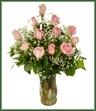 Offer your eternal love and adoration with one dozen soft pink roses arranged with baby's breath and lush greens in a clear glass vase.