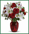 Add some romance with this rich arrangement of luxurious flowers in classic Valentine's colors. Red roses, white lilies and playful daisies are gathered in a ruby red vase!